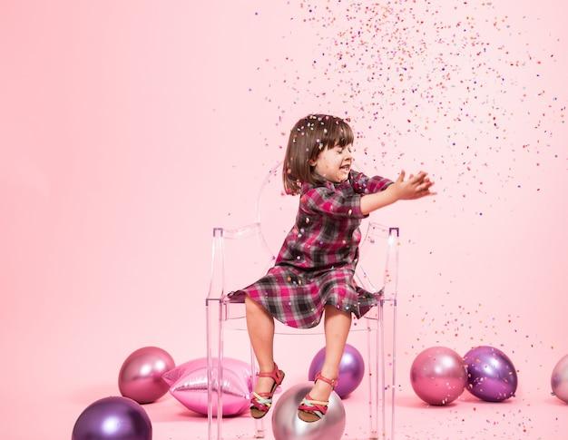 Маленькая девочка с удовольствием с конфетти. концепция праздника и веселья. Бесплатные Фотографии
