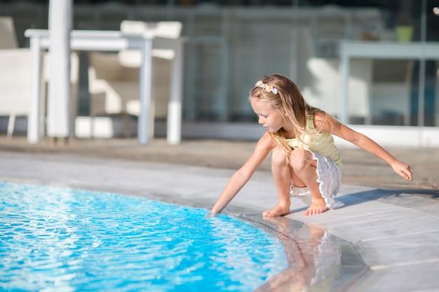 Little girl having fun with a splash near swimming pool Premium Photo