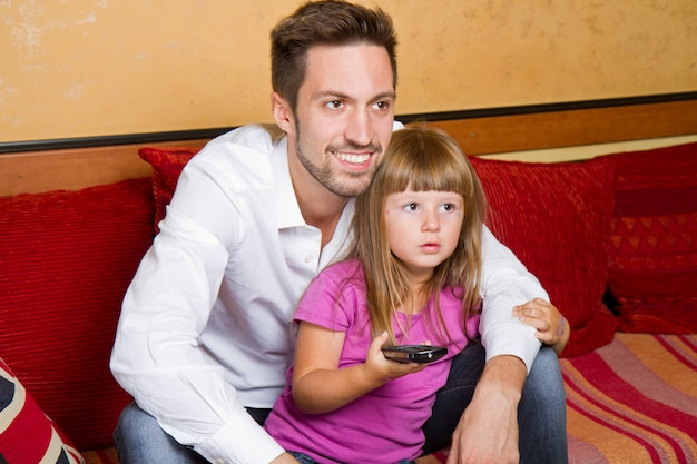 Little girl and her brother enjoy eating popcorn and watching tv Premium Photo