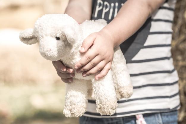 Маленькая девочка держит игрушечную овечку Бесплатные Фотографии