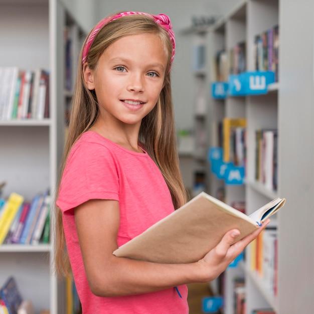 Bambina che tiene un libro in biblioteca Foto Gratuite