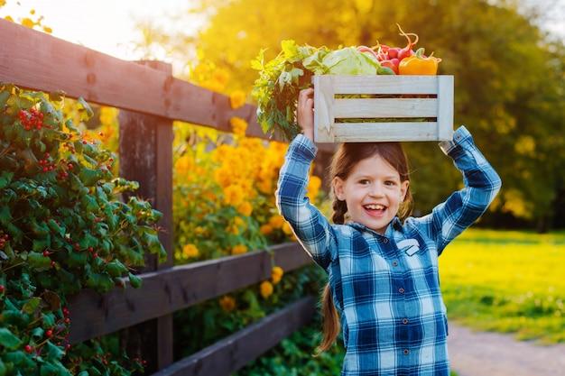 Little girl holding box of fresh organic vegetables Premium Photo