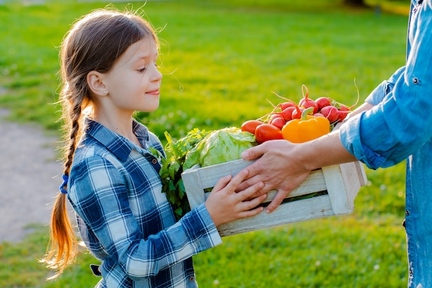 Little girl holding box of fresh organic vegetables Premium Photo