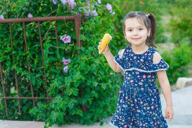 トウモロコシを押しながら春のドレスで庭でカメラ目線と幸せそうに見えて小さな女の子。正面図。 無料写真