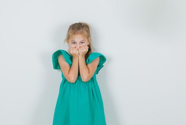 緑のドレスを着て顔に拳を持って、甘く見える少女 無料写真