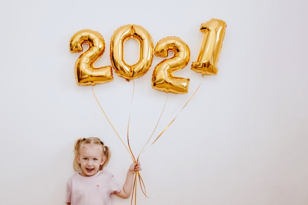 Little girl holding golden balloons with golden numbers Premium Photo