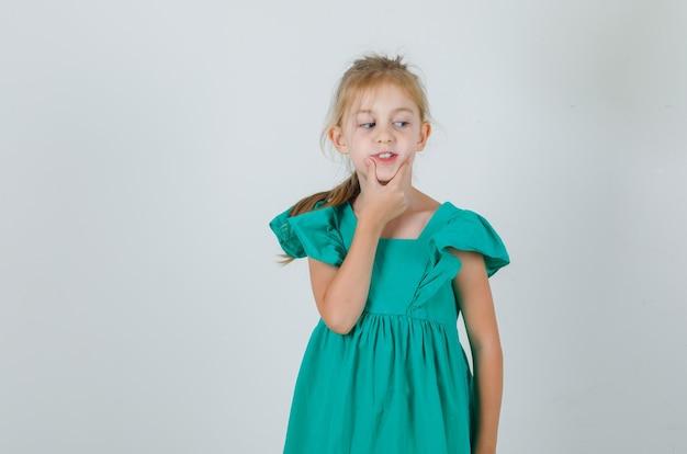 Маленькая девочка держит руку на подбородке в зеленом платье и выглядит мило. передний план. Бесплатные Фотографии