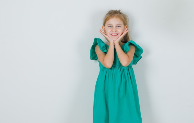 Bambina che tiene le mani sotto il mento in vestito verde e che sembra carina Foto Gratuite