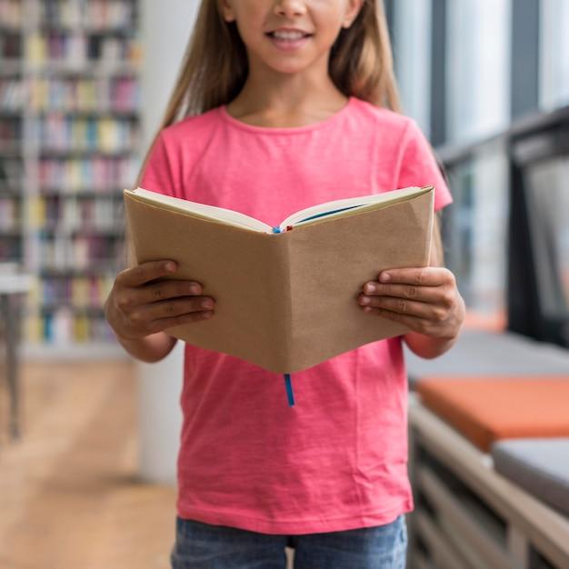Bambina che tiene un libro aperto Foto Gratuite