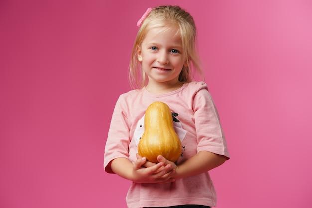 Маленькая девочка держит тыкву в руках Premium Фотографии