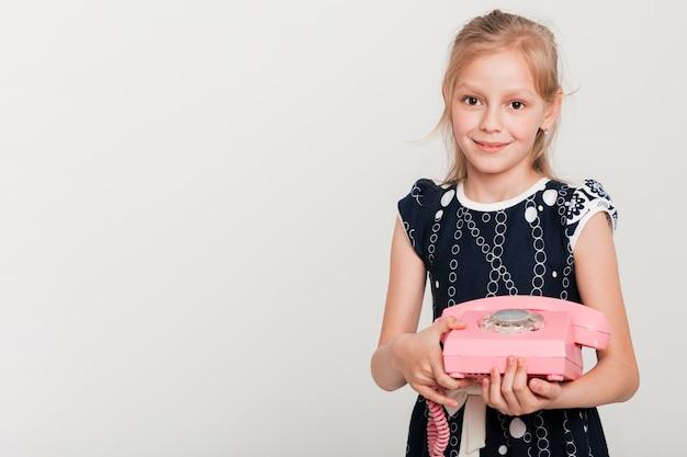 Little girl holding retro telephone Free Photo