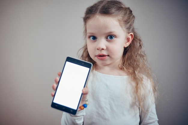 Little girl holding a smartphone with a white screen Premium Photo