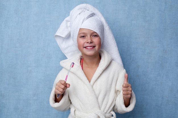 Little girl holding a toothbrush in her hand and showing thumbs up gesture Premium Photo