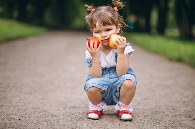 Little girl holding two apples Free Photo