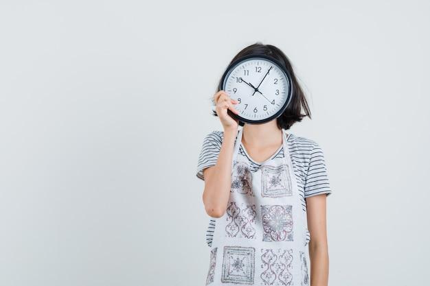 Bambina che tiene orologio da parete sul viso in t-shirt, grembiule Foto Gratuite