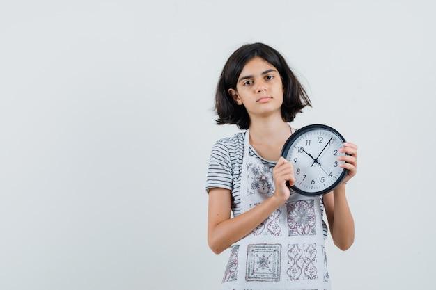 Bambina che tiene orologio da parete in t-shirt, grembiule e che sembra calma, Foto Gratuite