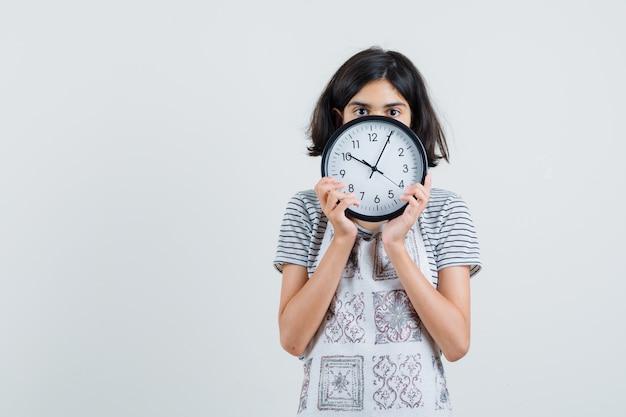 Bambina con orologio da parete in t-shirt, grembiule, Foto Gratuite