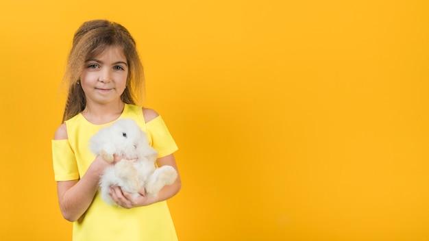 Little girl holding white rabbit Free Photo