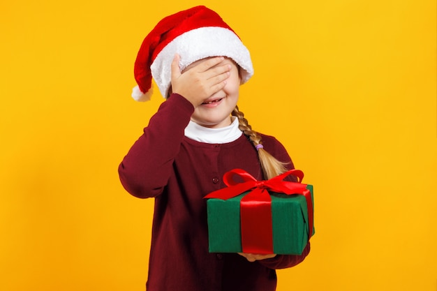 Little girl holds a box with a gift and closed her eyes with her hand. Premium Photo