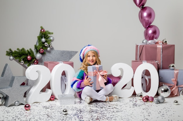 2020 Big Christmas Box Gifts Premium Photo | Little girl in holiday decor on light , gift boxes