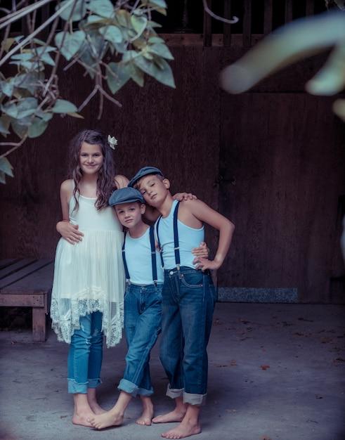 フェンスと緑に囲まれた2人の兄弟を抱き締める少女 無料写真