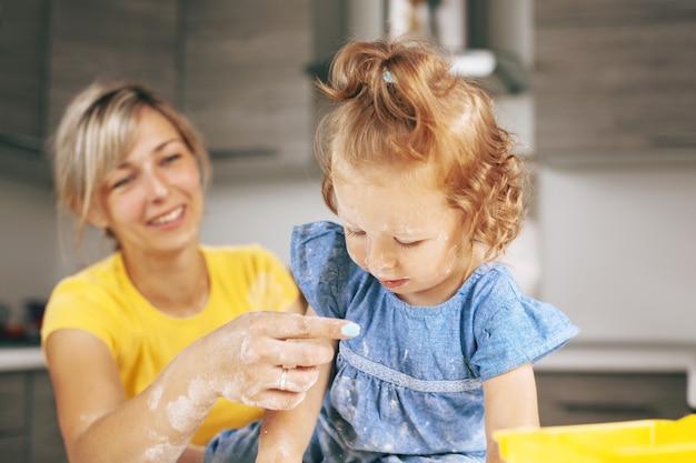 小麦粉で覆われた青いドレスの少女が母親の手を見てください。 Premium写真