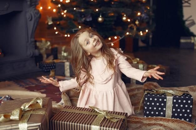 현재 크리스마스 트리 근처 귀여운 드레스 소녀 무료 사진