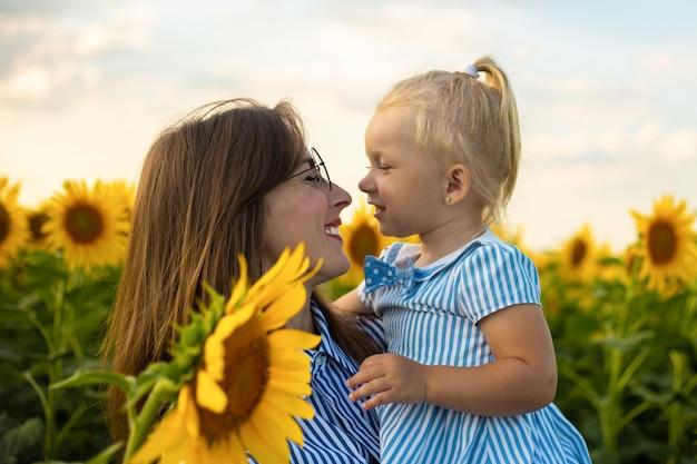 ドレスと眼鏡をかけた少女は、ひまわり畑で母親を見ています。フレンドリーな家族。 Premium写真