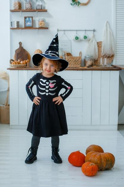 Маленькая девочка в костюме ведьмы Premium Фотографии