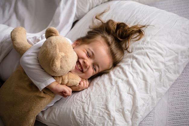 Маленькая девочка в постели с мягкой игрушкой эмоции ребенка Бесплатные Фотографии