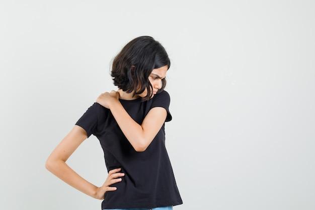 Маленькая девочка в черной футболке испытывает боль в шее и выглядит неудобно, вид спереди. Бесплатные Фотографии
