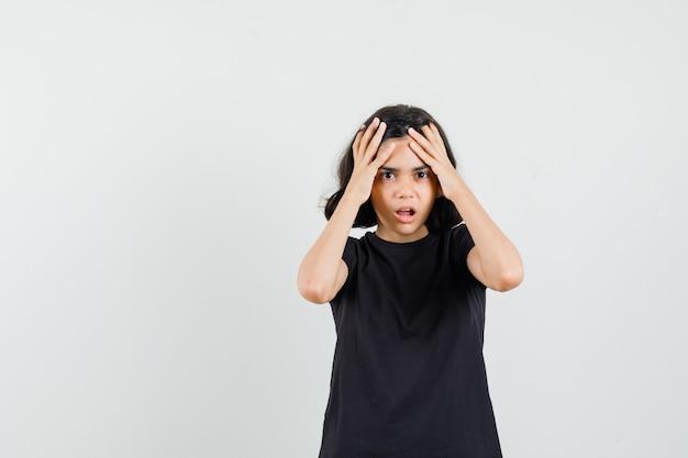 Маленькая девочка в черной футболке, взявшись за руки к голове и глядя печально, вид спереди. Бесплатные Фотографии