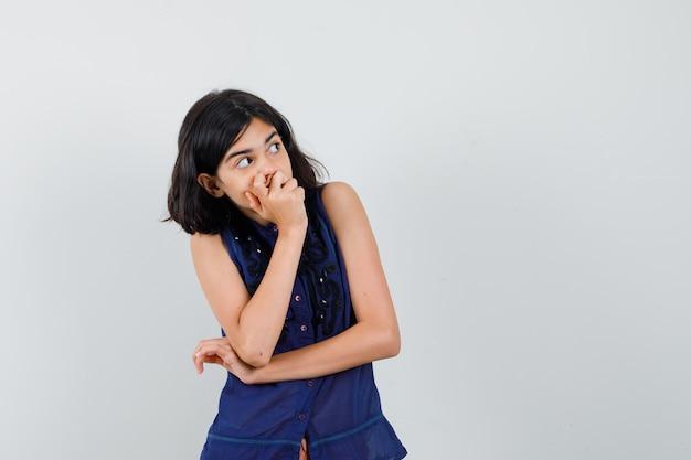 口に手をつないで、見上げて好奇心旺盛な青いブラウスの少女、正面図。 無料写真