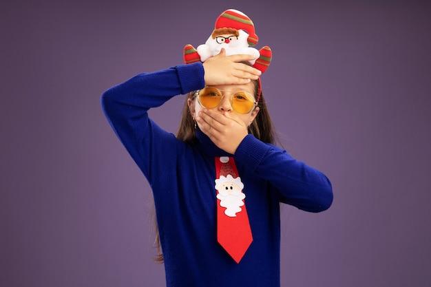 Маленькая девочка в синей водолазке с красным галстуком и забавной рождественской оправой на голове обеспокоена рукой на ее лбу и c Бесплатные Фотографии