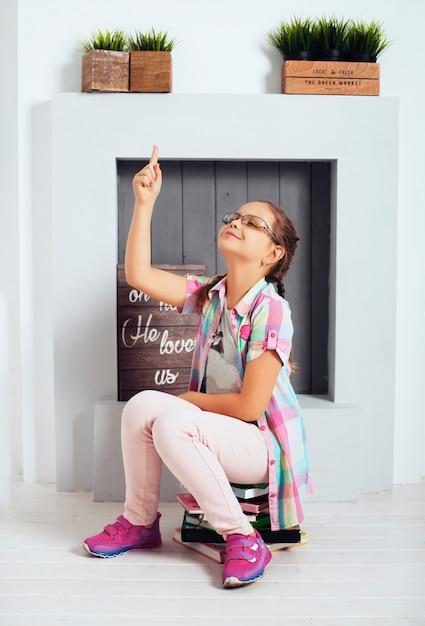 Маленькая девочка в очках сидит на книги. концепция образования Premium Фотографии