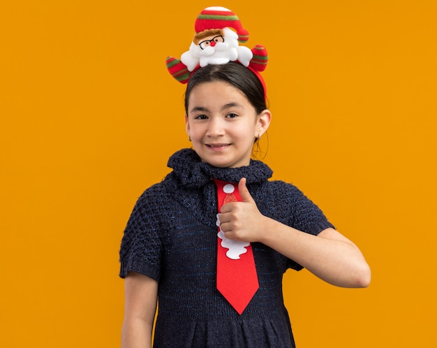 ニットのドレスを着た少女は、頭に面白いクリスマスの縁が付いた赤いネクタイを着て、親指を立てて幸せでポジティブに見えます 無料写真