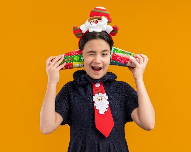 頭に面白いリムと赤いネクタイを着て、彼女の耳にカラフルな紙コップを持って混乱しているように見えるニットドレスの少女は元気に笑っています 無料写真