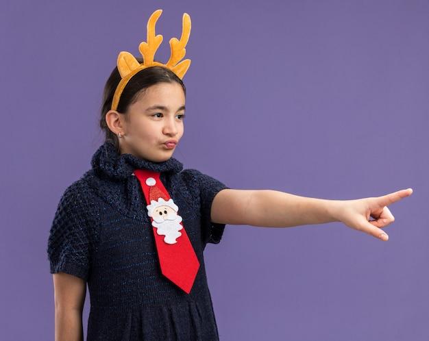 人差し指で何かを指して脇を見て頭に鹿の角を持つ面白いリムと赤いネクタイを着ているニットドレスの少女 無料写真
