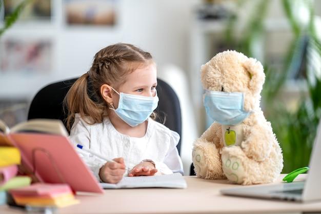 宿題をしているテディベアとマスクの少女。コロナウイルス予防 Premium写真