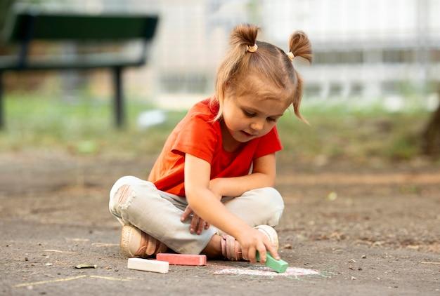 Маленькая девочка в парке, рисование мелом Бесплатные Фотографии