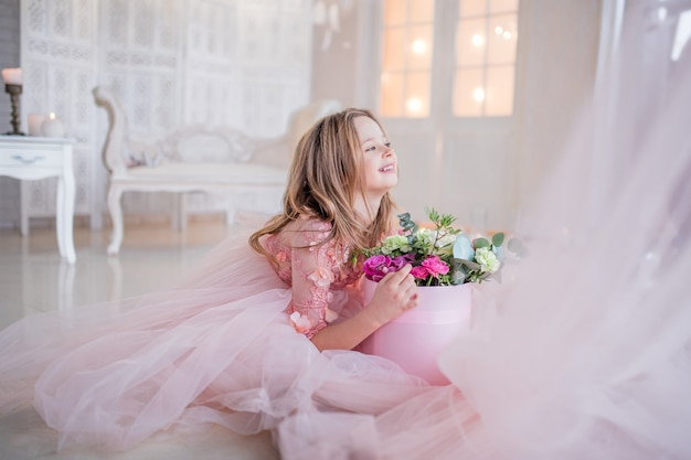 Little girl in pink dress holds box with roses sitting on the floor in a luxury room Free Photo