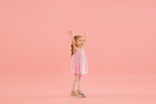 ピンクの壁にピンクのドレスを着た少女 無料写真