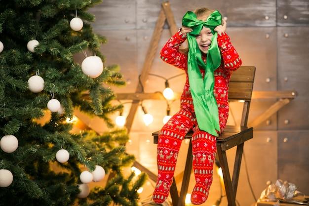 木製の椅子のクリスマスツリーによるパジャマの少女 無料写真