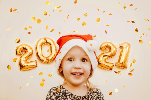 황금 숫자의 배경에 산타 모자 미소 어린 소녀 프리미엄 사진