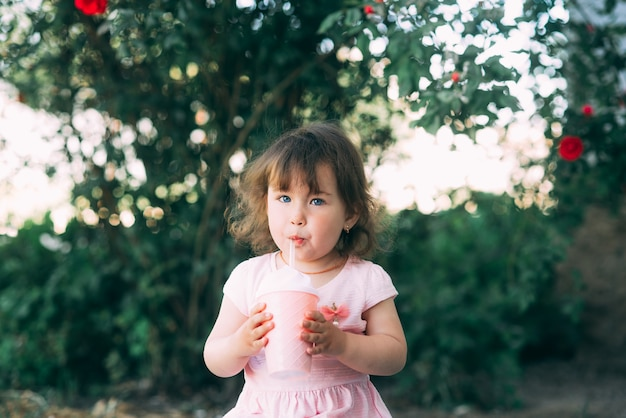 칵테일 컵에서 음료를 마시는 식물 정원에서 어린 소녀 프리미엄 사진