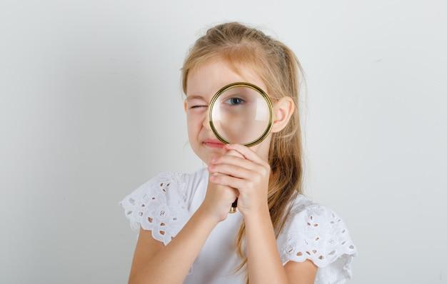 虫眼鏡を通して見る白いtシャツの少女 無料写真