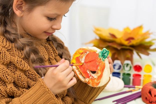 Маленькая девочка раскрашивает тыквы для веселой вечеринки в честь хэллоуина. Premium Фотографии