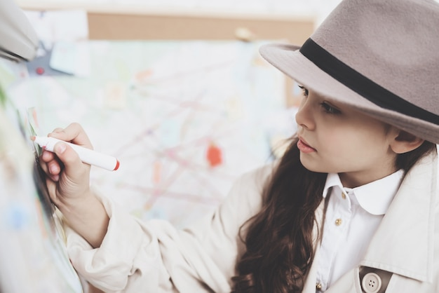 Little girl is drawing with marker on clues board. Premium Photo