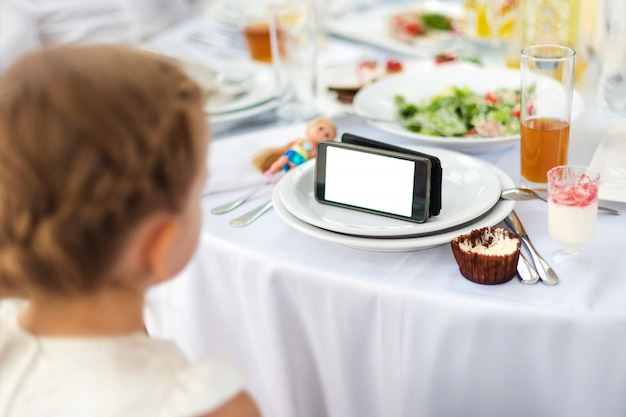 Little girl is having meal while watching the movie on the tablet. kid using phone, watching cartoons, addicted game and cartoon Premium Photo