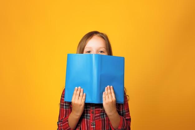 A little girl is hiding behind an open book Premium Photo